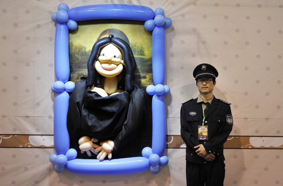 a-security-guard-stands-next-to-a-balloon-art-piece-depicting-mona-lisa-by-leonardo-da-vinci-at-a-balloon-themed-carnival-in-hefei-china