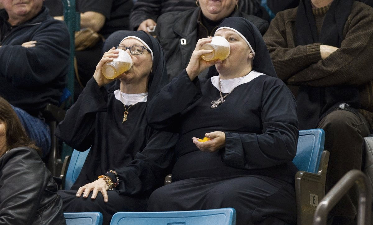 two-women-wearing-nun-outfits-drink-beer-while-watching-the-playoff-draw-between-quebec-and-manitoba-at-the-2014-tim-hortons-brier-curling-championships-in-canada-on-march-8